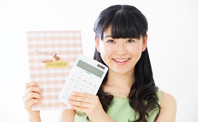 電卓と家計簿を持つ女性